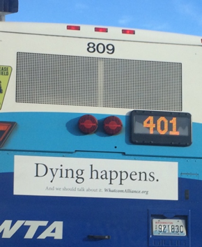 "a ""dying happens"" banner on the back of a WTA bus"