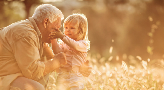 An elder man crouches to hug a little girl in a field of flowers