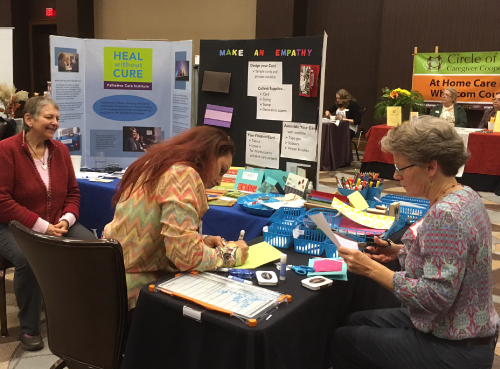 Two women sit at a table and create cards